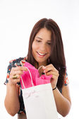 Young female girl holding gift bags in her arms, isolated on white — Stock Photo