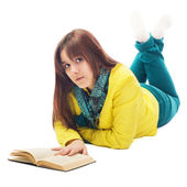 Portrait of a teenager lying on the floor reading book isolated on white — Stock Photo