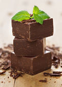 Closeup pieces of chocolate parts and mint leaves on wooden bac — Stock Photo