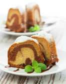 Vanilla and chocolate cake sliced with mint laves on wooden tab — Stok fotoğraf
