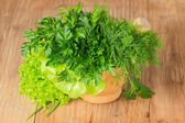 Green herbs in a pounder isolated on wooden table — Stock Photo