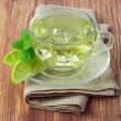 Cold green tea with ice cubes, lime sliced and mint leaves — Stock Photo