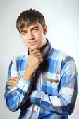 Portrait of casual young man looking at camera with arms crossed — Stock Photo