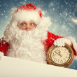 Santa Claus with white blank banner holding a clock showing sev — Stock Photo