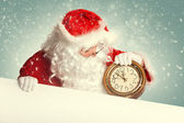 Santa Claus with white blank banner holding a clock showing sev — Foto Stock