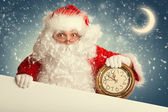 Santa Claus with white blank banner holding a clock showing sev — Foto de Stock