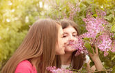 Two young women walking outside in a park at the violet lilac tr — Stock Photo