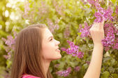 Young women walking outside in a park at the violet lilac tree — Stock Photo