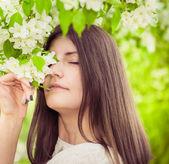 Beautiful spring brunette girl in blooming garden — Stock Photo