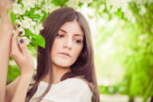 Beautiful spring brunette girl in blooming garden — Stock Photo