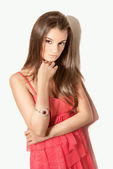 Beautiful brunette woman model posing in red dress in the studio — Stock Photo