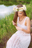 Cute young woman with circlet of camomile at the riverside — Stock Photo