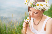 Cute young woman with circlet of camomile braiding her hair at t — Стоковое фото