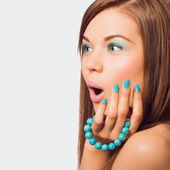 Young surprised woman holding a turquoise bracelet with bright m — Stock Photo