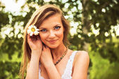 Young beautiful woman outdoor in a birchwood with daisy flowers — Stock Photo