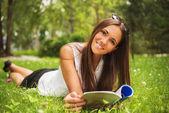 Una joven morena tirado en el césped al aire libre con una nuestra revista — Foto de Stock