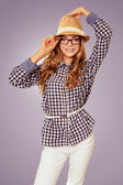 Young pretty womanl with retro garb touching her hat and glasses — Stok fotoğraf