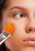 Woman applying foundation — Stockfoto