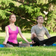 Woman and man doing yoga exercise — Stock Photo
