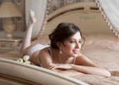 Woman in lingerie lying on bed — Stock Photo