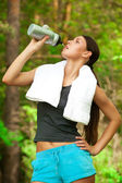 Woman drinking water after fitness — Stock Photo