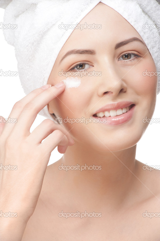 Portrait of young beautiful woman applying moisturizing cream on her face, isolated on white background  Stock Photo #15274193