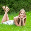 Girl lying on grass in park - Stockfoto