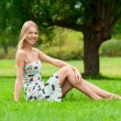Girl sitting on grass in park - Stockfoto
