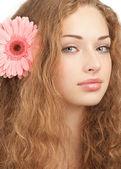 Bella donna con un fiore tra i capelli — Foto Stock
