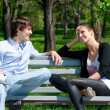 Couple sitting together on park bench — Stock Photo