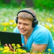 Young man using a laptop and listening music — Stock Photo