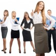 Happy business woman with colleagues standing in the background - Stock Photo