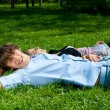 Young couple lying on the grass in park — Stock Photo