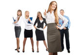 Happy business woman with colleagues standing in the background — Stock Photo