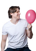 Handsome young man with a pink balloon — Stock Photo