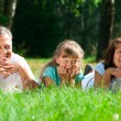Family lying on grass — Stock Photo
