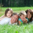 Family lying on grass — Stock Photo #15530105