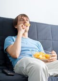 Young man watching tv and eating chips — Stock Photo
