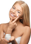 Beautiful woman applying moisturizer cream — Stock Photo