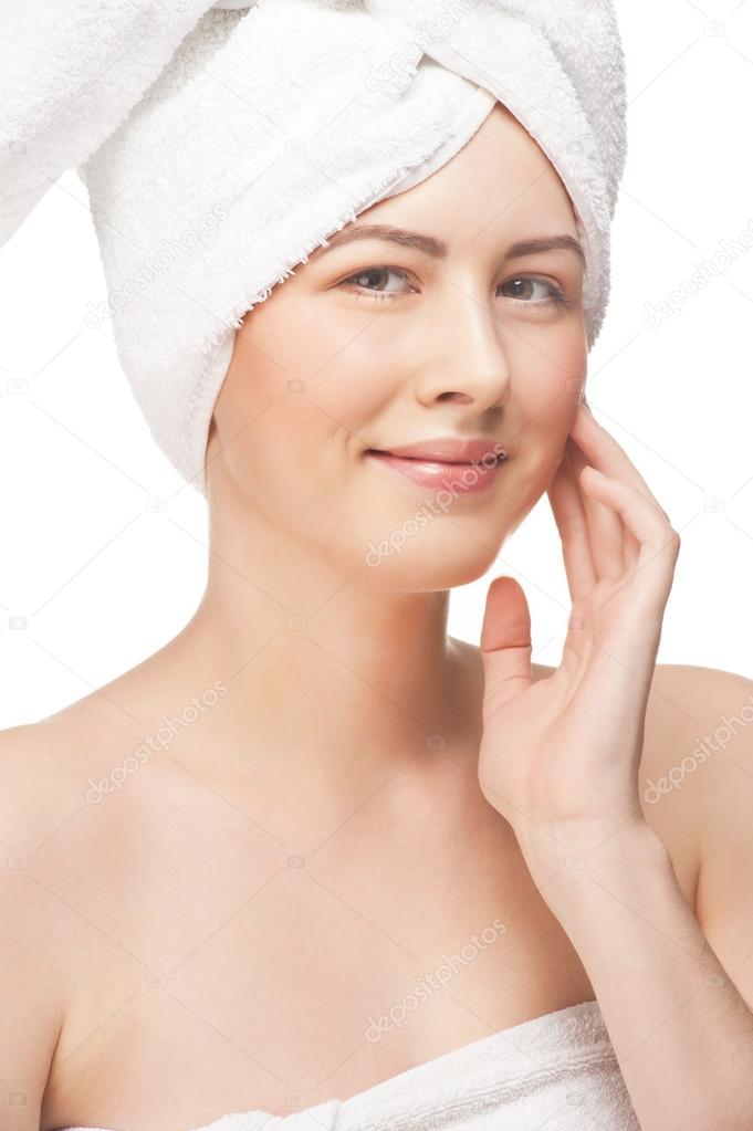 Portrait of young beautiful woman in white towel with healthy skin touching her face, isolated on white background — Stock Photo #15539693