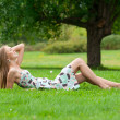 Girl lying on grass in park - Lizenzfreies Foto