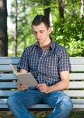 Libro de lectura joven al aire libre — Foto de Stock