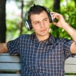Portrait of a young man listening to music outdoors — Stock Photo
