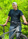 Man with cycle in park — Stock Photo