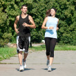 Fitness couple jogging in park - Stock Photo