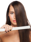 Woman with hair straightening irons — Stock Photo