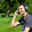 Portrait of a young man listening to music outdoors - Stock Photo
