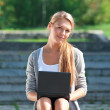 Business woman using laptop outdoors — Stock Photo