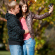 Young couple taking pictures of themselves in park — Stock fotografie