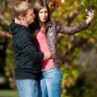 Young couple taking pictures of themselves in park — Stok fotoğraf